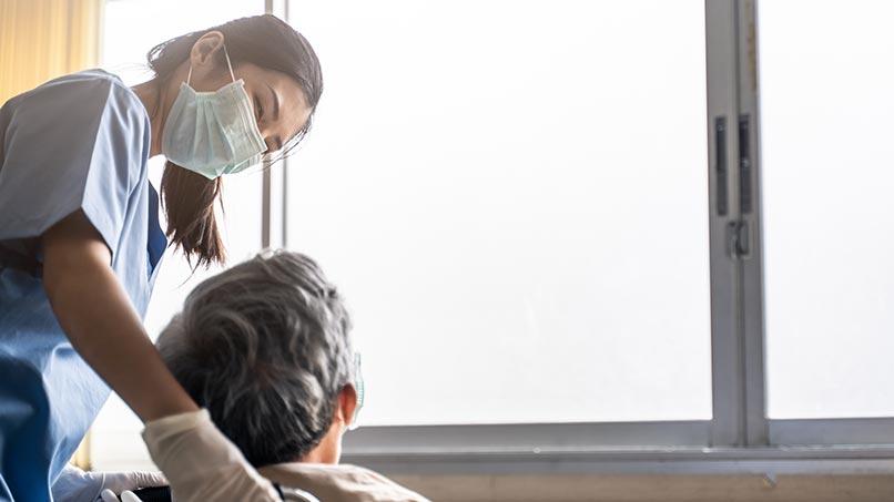 nfermeira asiática cuidando de pacientes maduros sentado em cadeira de rodas