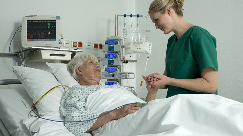 Idosa hospitalizada conversando com a enfermeira